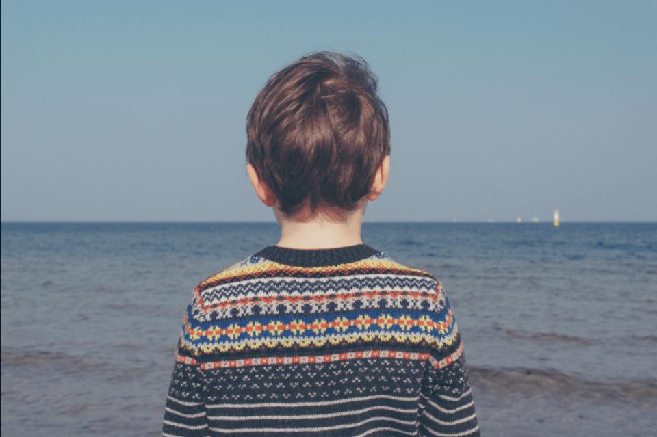 menino-de-costas-olhando-o-mar